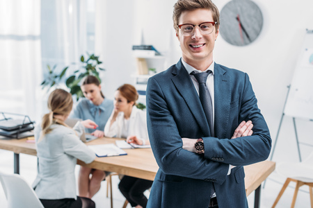 selective focus of cheerful recruiter in glasses standing with crossed arms near coworkers