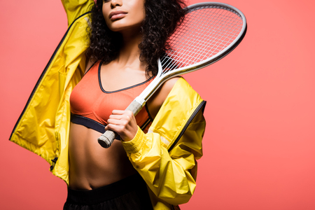 Cropped view of African American sportswoman holding tennis racket isolated on coral color background Reklamní fotografie