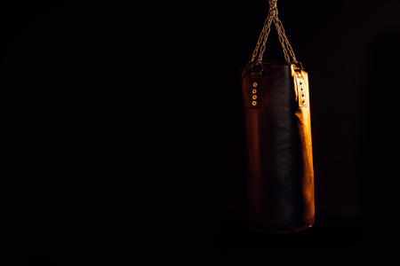 Leather punching bag hanging on steel chains isolated on black background