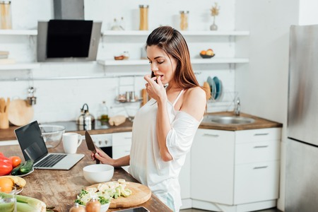 Young woman with knife cooking salad at table in kitchen