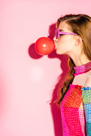 Attractive girl in sunglasses blowing red bubble gum on pink background