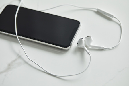 smartphone with blank screen and wired earphones on white marble surface