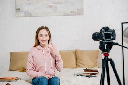Joyful teenage blogger showing peace sign at video camera Stock fotó