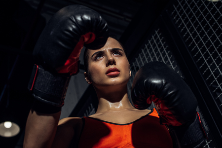 Low angle view of boxer in boxing gloves looking away