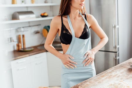 Cropped view of sexy woman in black underwear wiping hands with apron in kitchen