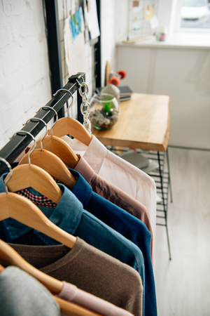 Straight rack with shirts on wooden hangers in room