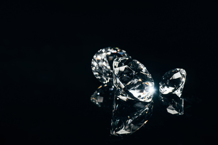 transparent pure diamonds isolated on black with reflection
