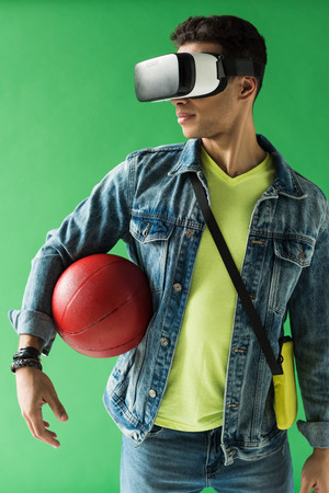 Mixed race man in virtual reality headset holding basketball on green screen