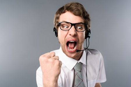 Angry call center operator in headset and glasses yelling and showing fist on grey background
