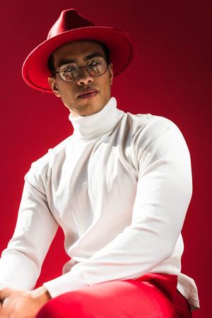 Moda hombre de raza mixta con sombrero y gafas sentado y posando aislado en rojo Foto de archivo