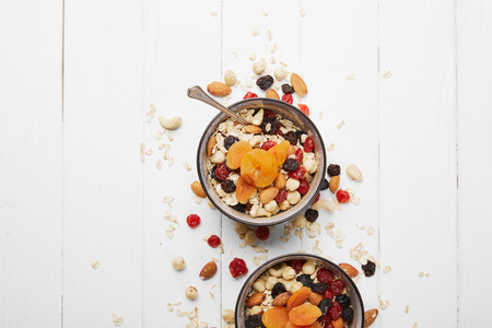 top view of bowls with muesli, dried apricots and berries and nuts served for breakfast with scattered ingredients on white table 免版税图像