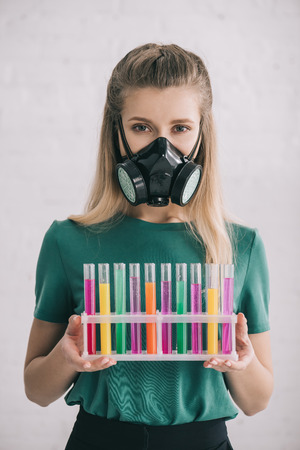 Blonde woman in respiratory mask holding colorful test tubes