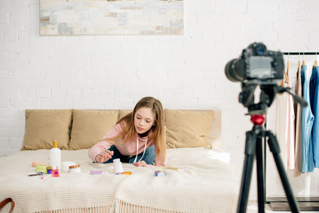 Teenage kid sitting on bed with cosmetics in front of video camera Stock Photo