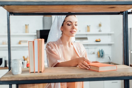 Curious woman in housecoat with towel on head holding book 写真素材