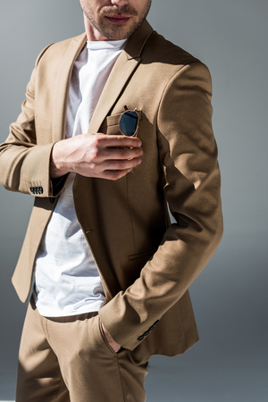 cropped view of man in beige suite with hand in pocket on grey