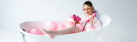 Panoramic shot of girl in sunglasses looking at pink retro phone while lying in bathtub with air balloons on white background 写真素材