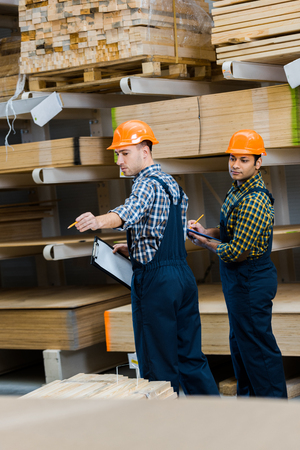 Two multicultural workers with clipboards standing near wooden construction materials