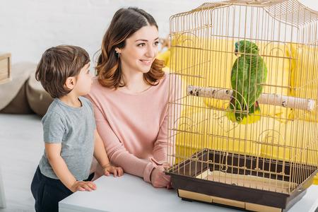 Femme séduisante souriante avec un fils adorable regardant un perroquet vert dans une cage à oiseaux