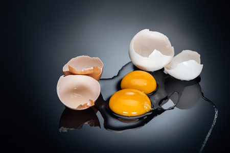 Raw smashed chicken eggs with yolks, proteins and eggshell on black background Stok Fotoğraf