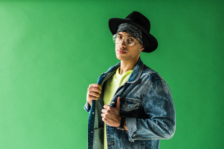 Stylish mixed race man posing and looking at camera on green screen with copy space
