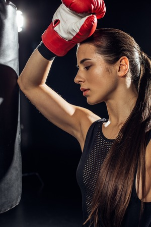 Tired boxer with ponytail standing near punching bag on black background
