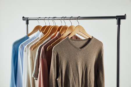 Straight rack, wooden hangers and male clothes isolated on grey background