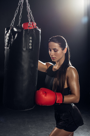 Female boxer in red boxing gloves training with punching bag