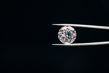 Transparent pure shiny diamond in tweezers isolated on black background