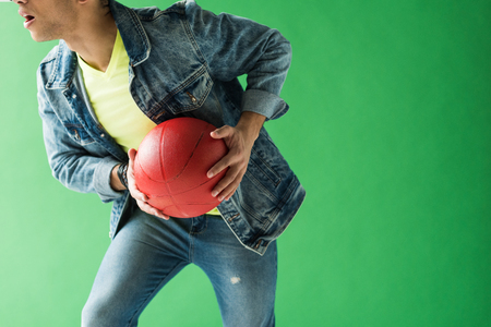 Cropped view of mixed race man in denim holding basketball on green screen with copy space