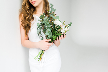 Cropped view of girl holding bouquet of flowers on white background