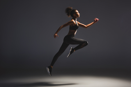 Side view of beautiful athletic African American sportswoman jumping on black background