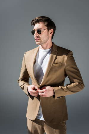 Serious stylish man in beige suite and sunglasses looking away on grey background