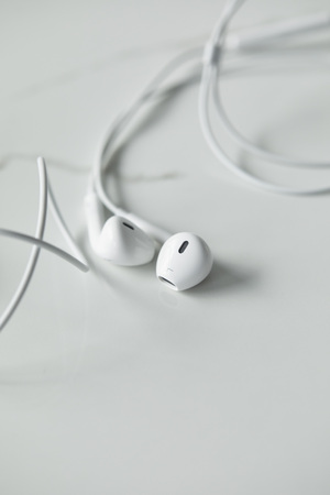Selective focus of white wired earphones on white surface with copy space Stok Fotoğraf