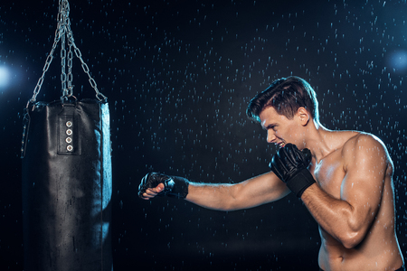 Boxer training with punching bag under water drops on black background