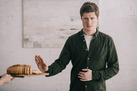 Cropped view of woman holding cutting board with bread near handsome man with gluten allergy Stock Photo