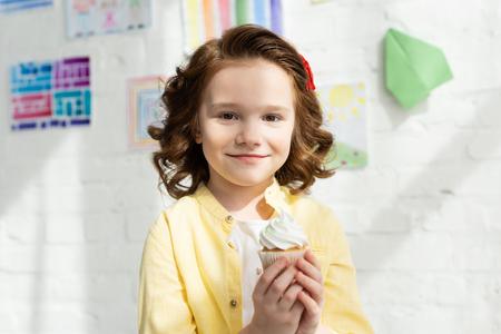 Adorable kid holding delicious cupcake and looking at camera at home