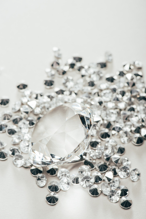 Selective focus of transparent pure big diamond among small on white background
