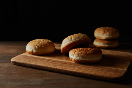Delicious buns with sesame on wooden chopping board isolated on black background