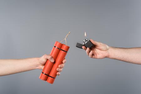 Ausgeschnittene Ansicht von Männern, die Dynamit und Feuerzeug auf grauem Hintergrund halten