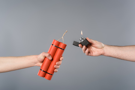 Cropped view of men holding dynamite and lighter on grey background