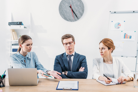 Attractive recruiter gesturing near coworker in glasses sitting with crossed arms