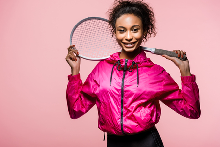 Beautiful African American sportswoman holding tennis racket, looking at camera and smiling isolated on pink background Imagens