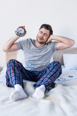 Handsome man stretching and holding alarm clock while sitting on bedding Stock Photo