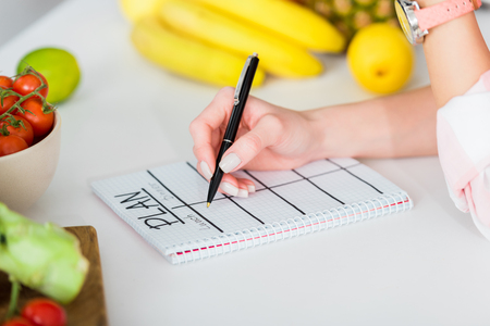 Cropped view of woman writing in notebook with plan lettering near ingredients