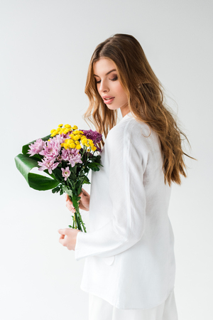 Attractive girl looking at bouquet of wildflowers on white background Reklamní fotografie