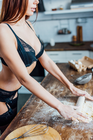 Cropped view of woman in black lingerie rolling out dough with rolling pin