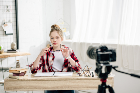 Teenage blogger sitting at desk in front of video camera and making video
