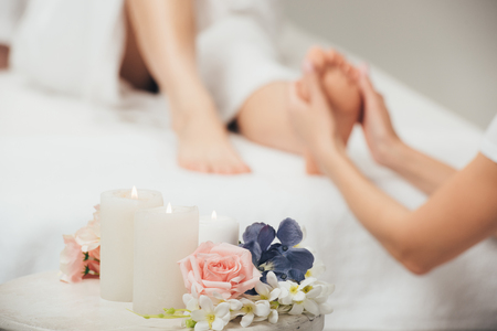 Selective focus of masseur doing foot massage to adult woman in spa
