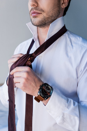 cropped view of confident man in white shirt putting tie on Imagens
