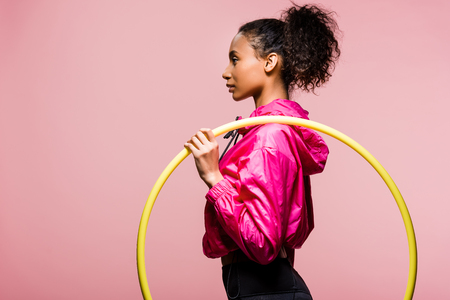 side view of beautiful african american sportswoman posing with hula hoop isolated on pink with copy space